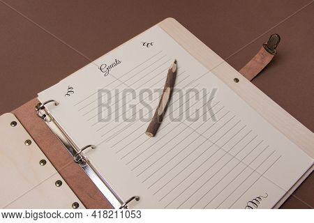 Wooden Guests Book With Pen On Brown Colored Paper Background. Close Up.