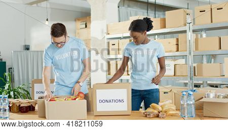 Social Help. Volunteers Man And Woman Collecting Food Donations In Warehouse. Social Workers Putting