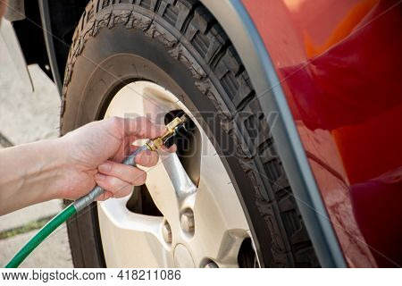 Hand Holding Pressure Gauge, Checking Air Pressure And Filling Air In The Tires Of The Car. Car Main