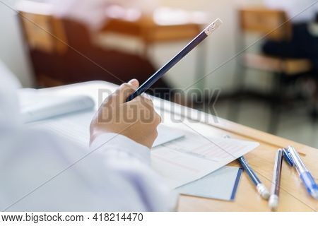 Concentration Of Student Reading Document Test Papers And Taking Exam Testing Or Study With Pencils