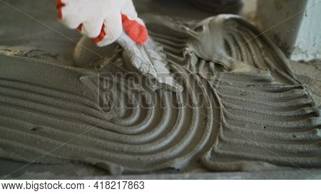 The Process Of Applying Mortar For Laying Ceramic Tiles. Leveling Ceramic Tile Mortar On The Floor.