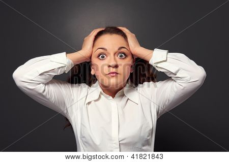 portrait of scared young woman over dark background