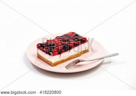 Slice Of Cheesecake With Raspberry And Currant Sauce In A Pink Plate, White Background, Closeup View
