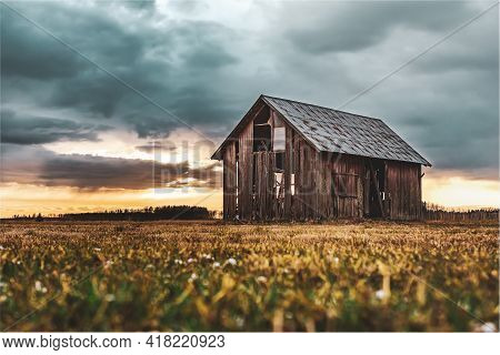 Old Barn Standing On Open Farmland During Sunset One Late Evening In April