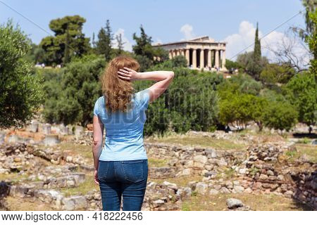 Young Woman Looks At Temple Of Hephaestus, Athens, Greece. This Ancient Greek Structure Is One Of Ma
