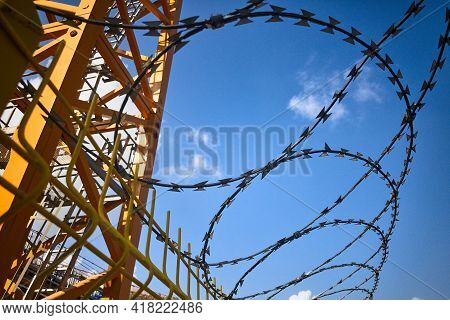 Barbed Wire On A Fence Around Construction Site Against Blue Sky. Restricted Area. Tower Crane Behin