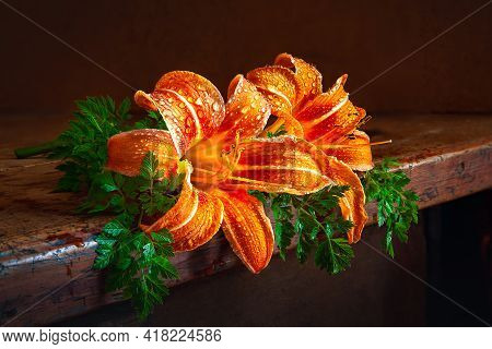 Lilies On A Wooden Table. Wet Garden Flowers Daylily In Drops Of Water On A Dark Background. Still L