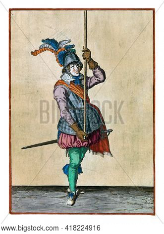 A soldier, full-length, holding a spear (lance) with both hands upright high above the ground in front of him. This is the second operation for raising the skewer upright