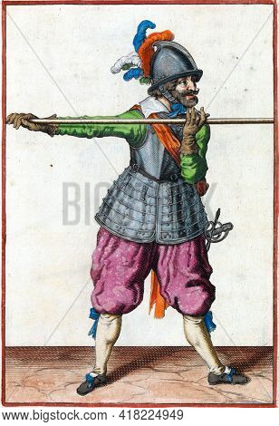 A soldier, full-length, carrying a spear (lance) with both hands horizontally at shoulder height.