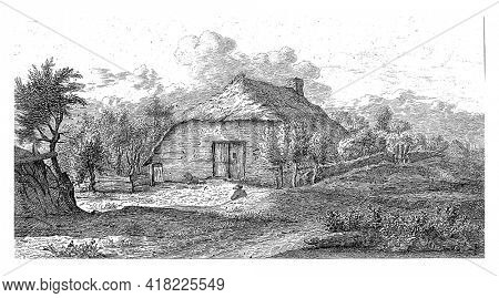 A farm with a straw roof. Trees to the left and behind the farm. In the foreground a man seen from behind.