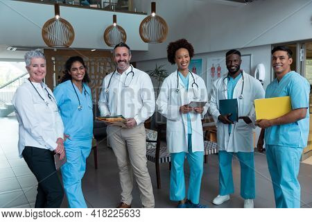 Portrait of group of diverse male and female doctors standing in hospital corridor smiling to camera. medicine, health and healthcare services.