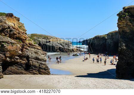 People Sunbathing On The Idyllic Las Catedrales Beach In Galicia Spain. Lugo