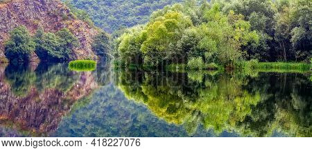 Panoramic Green Landscape Reflected In The Water From The Side Formed A Symmetrical Image. Asturias.
