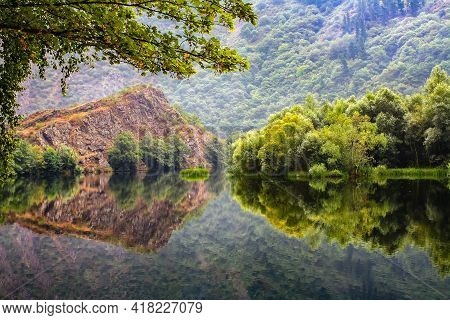 Lush Vegetation On The Shore Of The Lake With Reflections In The Calm Water. Asturias Spain. Europe.