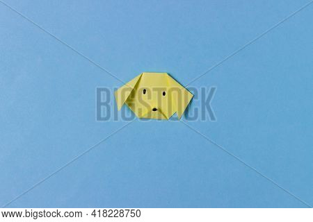 The Dog's Head Is Folded From Yellow Paper In The Technique Of Origami With Painted Mustache. Concep