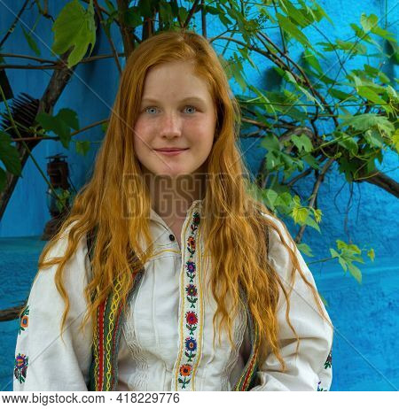 Salaj, Transylvania, Romania-may 14, 2018: Beautiful Freckled Young Girl With Red Hair And Blue Eyes