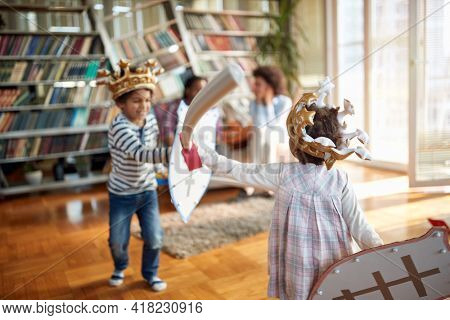 Kids are enjoying while playing with swords and shields in a cheerful atmosphere at home. Family, together, love, playtime