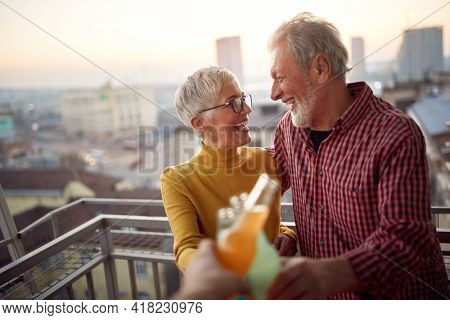 An elderly couple toasting and enjoying a drink with some company in a cheerful atmosphere on the terrace of an apartment at a beautiful sunset over the city. Spouses, pensioners, together, home