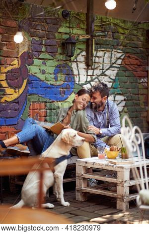 A young couple in love spending a wonderful time in a relaxed atmosphere at a bar together with their dog. Leisure, bar, friendship, outdoor