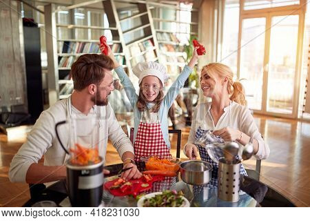 A young family is excited while preparing a meal in a cheerful atmosphere at home together. Family, together, home