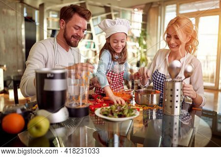 A little daughter helping her parents in meal preparation in a cheerful atmosphere at home. Family, together, home