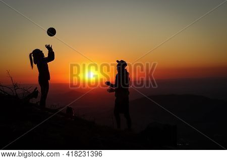 Young Volleyball Couple Enjoying The Top Of A Pink Mountain With A Ball At Sunset. Silhouettes Of A