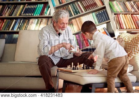 Grandpa and his little grandson having fun while playing the chess game in a playful atmosphere at home. Family, game, together