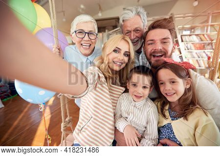 Three generation family taking a selfie in a cheerful atmosphere at home together. Family, leisure, together