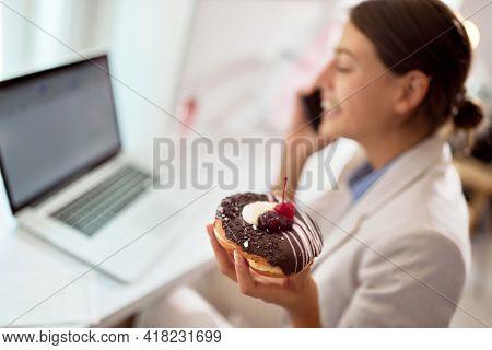 A young business woman talking on a smartphone while spending time in a pleasant atmosphere in a pastry shop eating delicious donut. Pastry shop, dessert, sweet