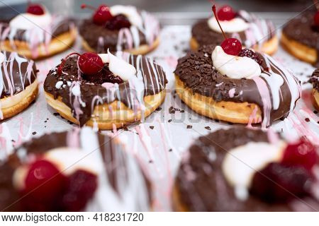 Delicious donuts of irresistible appearance with chocolate topping and cherry on the top on the tray ready for a pastry shop. Pastry, dessert, sweet