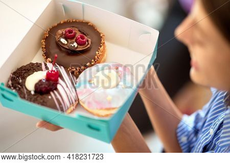 A beautiful girl in a pleasant atmosphere of a pastry shop is holding a box with delicious donuts. Pastry shop, dessert, sweet
