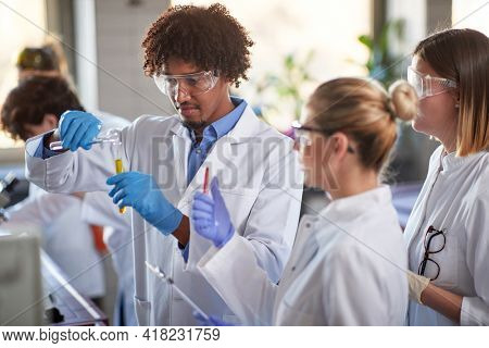 Young students mix chemicals in a test tube and discuss a chemical reaction in a sterile laboratory environment. Science, chemicals, lab, people