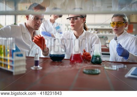 Young chemistry students work with dangerous chemicals in a working atmosphere in the university laboratory. Science, chemistry, lab, people