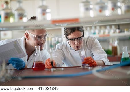 Young chemistry students in a protective gear analyze chemical reaction in a working atmosphere in the university laboratory. Science, chemistry, lab, people