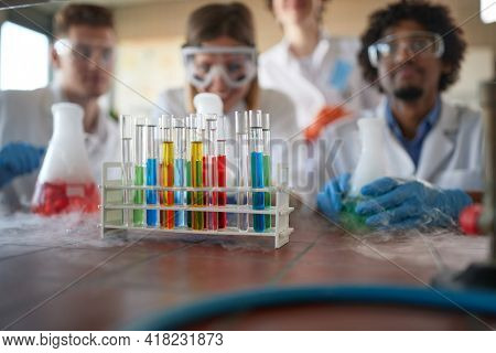 Young chemistry students in a sterile laboratory environment are enjoying observing colorful chemical reactions. Science, chemistry, lab, people