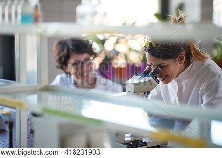 Young cheerful female chemistry students have a good time while working with a microscope in a laboratory in a relaxed atmosphere. Science, chemistry, lab, people