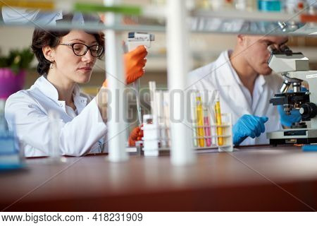 Young chemistry students are pipetting and microscoping in a laboratory in a working atmosphere. Science, chemistry, lab, people