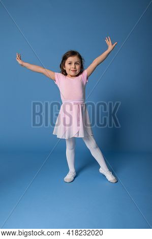 Full Length Portrait Of A Beautiful Child Ballerina Performing Ballet Dancing Isolated On Blue Backg