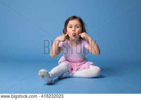 Cute Child Ballerina Grimacing And Showing Her Tongue Looking At Camera, Isolated Over Blue Backgrou