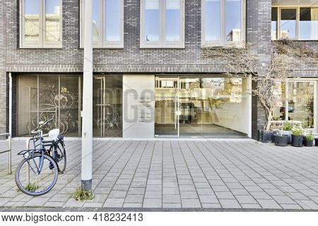 Paved Sidewalk With Bicycle And Potted Plants Located Near Entrance Of Contemporary Apartment Buildi