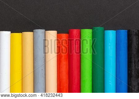 Row Of Colored Pastel Crayons For Drawing On A Black Paper Background. Close-up Top View