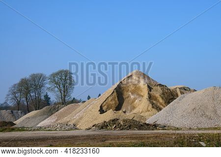 Mountains Of Rubble And Sand At A Construction Site. Clear Blue Sky Without Clouds.