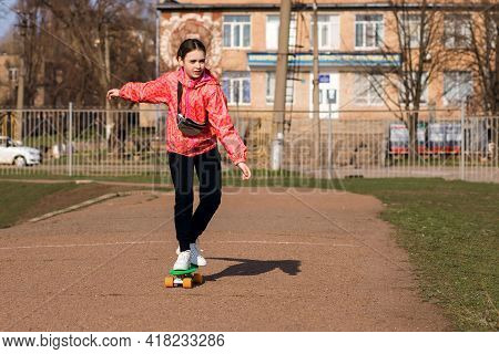 A Teenage Girl In Bright Clothes Is Riding A Skateboard Or Pennyboard In The Park. Skateboarding Is