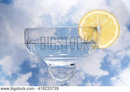 Coupe Cocktail Glass With A Lemon Wagon Wheel Garnish Against Cloudy Sky.