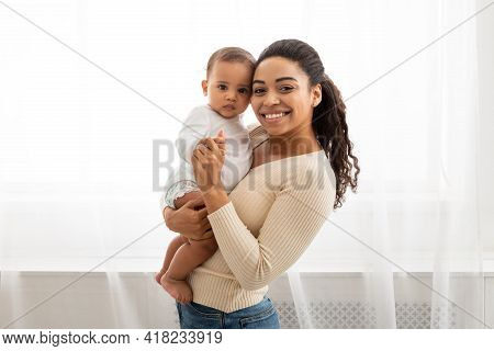 Black Mom Holding Little Infant Smiling To Camera Posing Indoors