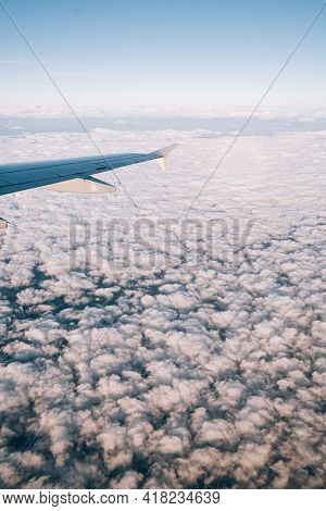 View From The Airplane Window On White Cumulus Clouds Below
