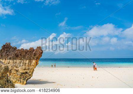 Zanzibar, Tanzania - February 12, 2020 : Tropical White Beach Of Zanzibar Island With A Rock, Tanzan