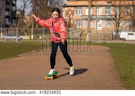 Teenage Girl On Vacation In Colorful Clothes Learns To Skateboard Or Pennyboard In The Park. An Acti