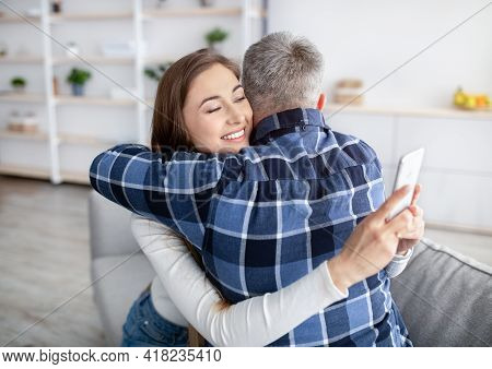 Gadget Addiction Or Infidelity. Mature Woman Hugging Husband, Stuck In Smartphone, Playing Online Ga