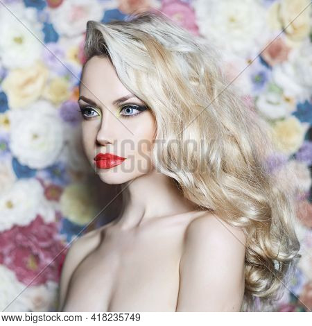 Fashion portrait of beautiful blonde on flower background. Sexy young woman with classic smoke-eyes makeup and curly hair